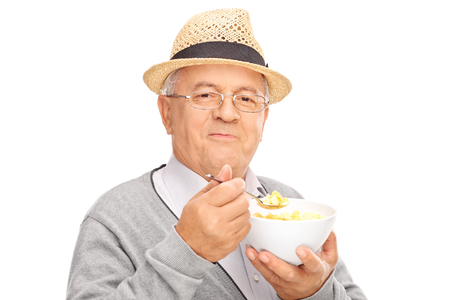 Studio shot of a senior gentleman eating cereal from a bowl and looking at the camera isolated on white background