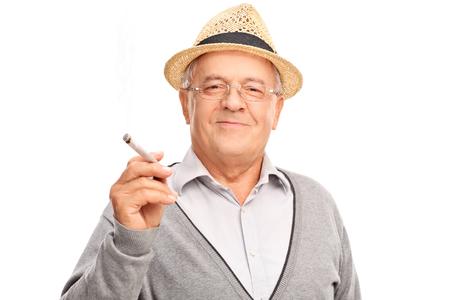 hombre fumando: Hombre maduro alegre que sostiene una articulación y mirando a la cámara aislada en el fondo blanco