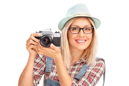 mujer alegre: Fotógrafo de sexo femenino rubia con una gorra azul que sostiene una cámara y posando aislados sobre fondo blanco