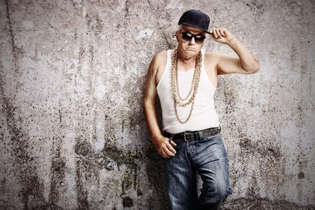 hip hop man: Senior gangster in hip hop outfit leaning against a rusty gray wall and looking at the camera Stock Photo