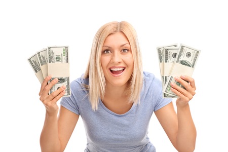overjoyed: Studio shot of an overjoyed woman holding few stacks of money and looking at the camera isolated on white background Stock Photo