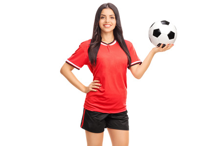 pelota de futbol: Jugador de f�tbol de sexo femenino joven en camiseta roja sosteniendo una pelota y sonriente aislados sobre fondo blanco Foto de archivo