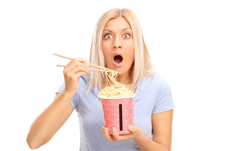 noodles: Shocked blond woman eating Chinese noodles and looking at the camera isolated on white background