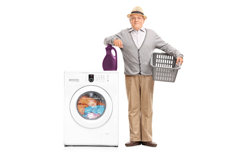 man laundry: Full length portrait of a senior gentleman standing next to a washing machine and leaning on a laundry detergent isolated on white background