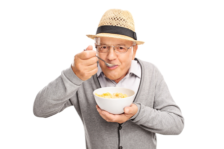 Senior man eating cereal with a spoon and looking at the camera isolated on white background Foto de archivo