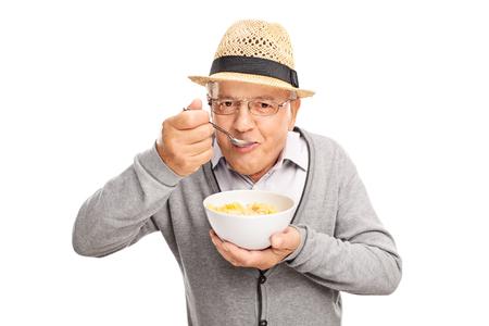 comiendo: Hombre mayor que come el cereal con una cuchara y mirando a la cámara aislada en el fondo blanco