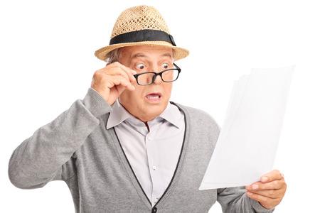 Geschokt senior man kijken naar de rekeningen in ongeloof op een witte achtergrond