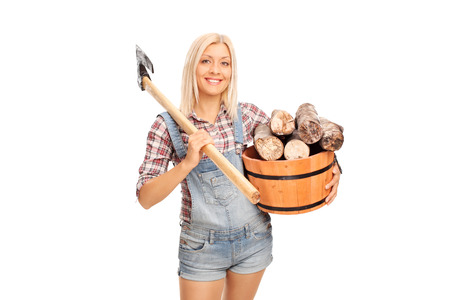 lumberjack shirt: Young blond woman in checkered shirt holding a bucket full of logs and carrying an axe over her shoulder isolated on white background