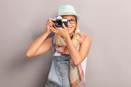 female photographer: Young female photographer photographing with a retro camera and smiling