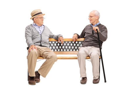 sit: Studio shot of a two senior men arguing with each other seated on a wooden bench isolated on white background Stock Photo