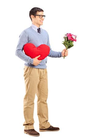 hombre romantico: Retrato de cuerpo entero de un hombre rom�ntico con un coraz�n rojo y un ramo de flores aisladas sobre fondo blanco Foto de archivo