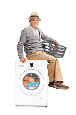 machine man: Vertical shot of a senior man waiting for the laundry seated on a washing machine isolated on white background
