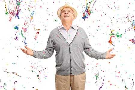tercera edad: Caballero mayor alegre de pie en un montón de serpentinas confeti aisladas sobre fondo blanco Foto de archivo