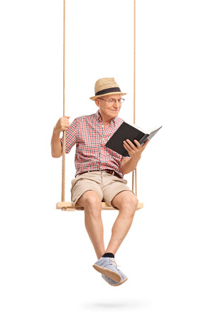 Joyful senior man sitting on a wooden swing and reading a book isolated on white background