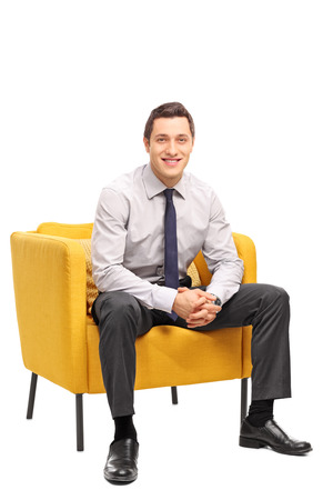 man sit: Vertical shot of a confident young businessman sitting in a yellow armchair and looking at the camera isolated on white background