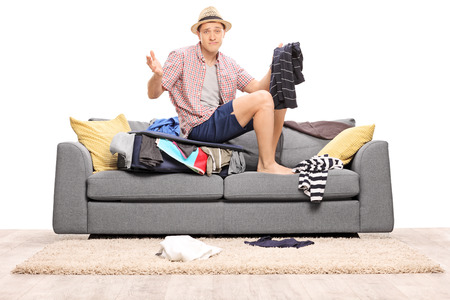 packing suitcase: Sad young man sitting on his overstuffed suitcase and gesturing with his hands isolated on white background