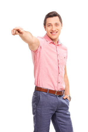 hand pointing: Vertical shot of a confident young man pointing forward with his hand and looking at the camera isolated on white background