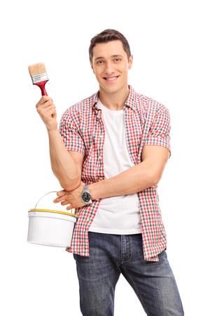 brocha de pintura: Tiro vertical de un joven alegre que sostiene una brocha y un cubo de color aislado en el fondo blanco