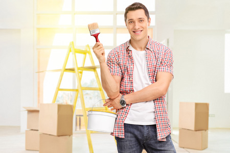 Cheerful man holding a paintbrush and a color bucket in a new apartment with a few cardboard boxes and a yellow ladder behind him Reklamní fotografie