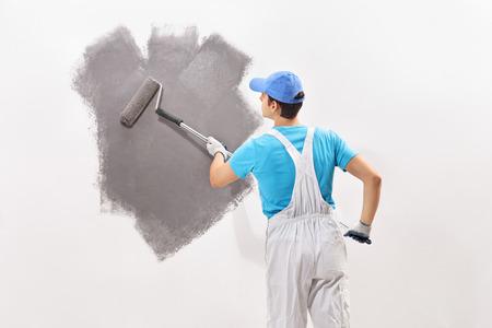 グレー色の壁を塗る白いオーバー オールで若い男性のデコレータの背面ショット
