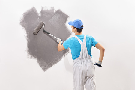 overalls: Rear view shot of a young male decorator in white overalls painting a wall with gray color