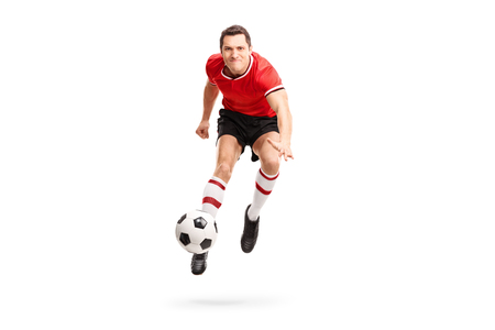 soccer player: Young sportsman kicking a football in mid-air and looking at the camera isolated on white background
