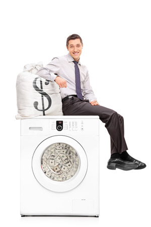 organized crime: Vertical shot of a young businessman sitting on a washing machine full of money and leaning on a bag with a dollar sign on it isolated on white background