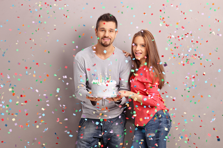Young joyful couple holding a birthday cake with a lot of confetti streamers flying around them Stock Photo