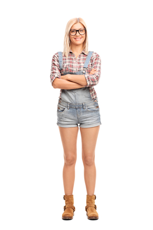 female pose: Full length portrait of a hipster girl with large black glasses and a short overalls isolated on white background