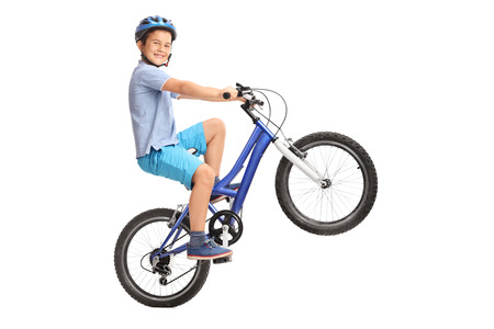 Joyful little boy performing a wheelie with his bike and looking at the camera isolated on white background