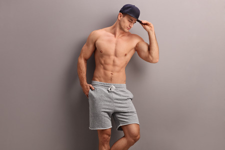 male body: Handsome shirtless man with a blue cap posing against a gray wall