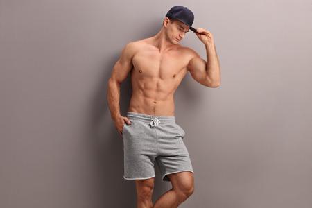 hombre sin camisa: Hombre descamisado hermoso con una gorra azul que presenta contra una pared gris