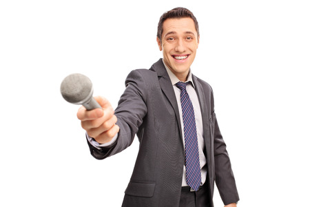 men in suit: Cheerful interviewer in a gray suit holding a microphone and looking at the camera isolated on white background Stock Photo