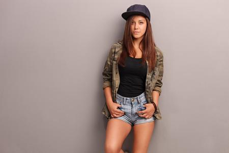 gorras: Adolescente fresca en ropa de moda apoyado contra una pared gris y mirando a la c�mara