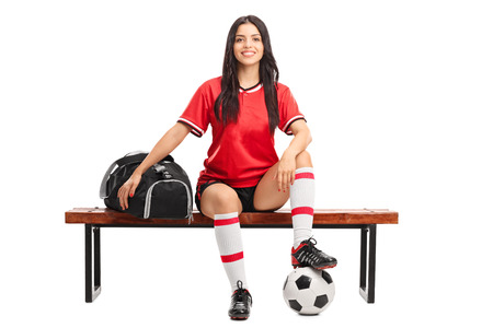 female soccer: Young female soccer player sitting on a wooden bench with a sports bag beside her isolated on white background