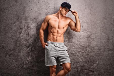 männer nackt: Gut aussehende shirtless Mann mit einer blauen Kappe lehnt an einem rostigen graue Wand und Blick nach unten Lizenzfreie Bilder