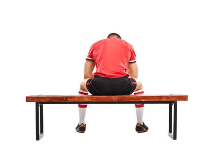 木製のベンチに座っているとの分離のホワイト バック グラウンドを見下ろす悲しい男性サッカー選手の背面ビュー スタジオ撮影
