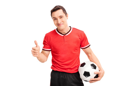 posing  agree: Studio shot of a happy young football player holding a ball and giving a thumb up isolated on white background Stock Photo