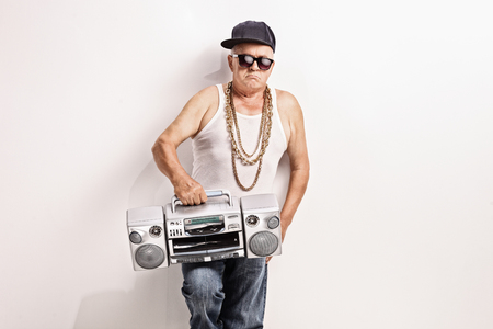 hip hop pose: Hardcore senior rapper holding a ghetto blaster and looking at the camera