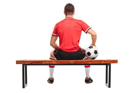 ボールを保持していると、白い背景に分離された木製のベンチに座っている男性のサッカー プレーヤーの背面ビュー スタジオ撮影