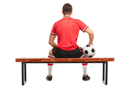 soccer player: Rear view studio shot of a male football player holding a ball and sitting on a wooden bench isolated on white background