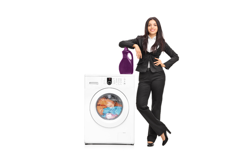 leaning: Full length portrait of a young businesswoman standing by a washing machine and leaning on a laundry detergent isolated on white background