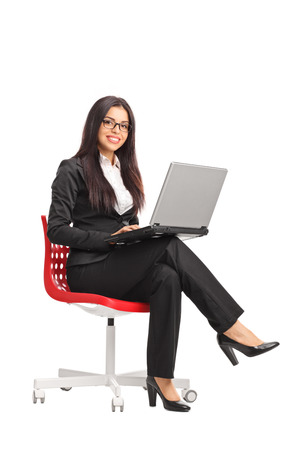easy chair: Vertical shot of a young businesswoman holding a laptop and looking at the camera seated on a red chair isolated on white background Stock Photo