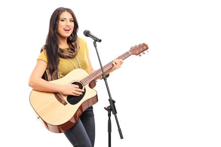 gitara: Kobieta muzyk gra na gitarze i śpiewa na mikrofon na białym tle