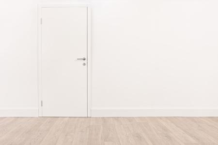 白い壁と明るい茶色の堅木張りの床の新しい白いドアのショット