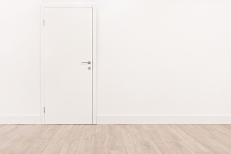 Colpo di una nuova porta bianca su una parete bianca e un pavimento in legno marrone chiaro