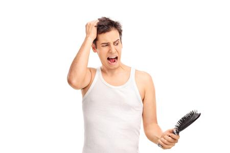 怒っている若い男髪を失うことと、白い背景で隔離のヘアブラシを保持