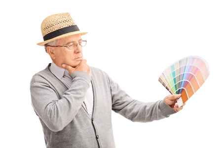 color swatch: Pensive senior gentleman looking at a color swatch and choosing a color isolated on white background