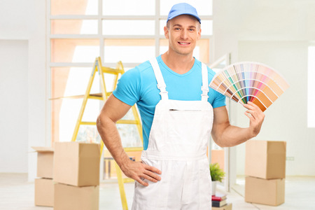 Young male house painter in a white jumpsuit holding a color swatch in an apartment and looking at the camera
