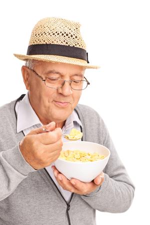 hombre comiendo: Primer plano de un señor mayor que come cereal con una cuchara de metal aisladas sobre fondo blanco